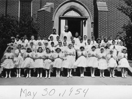 Students in the class of 1954 stand in front of St. Mary's Parish for a photo on May 30, 1954.