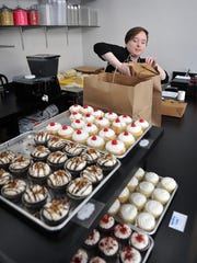Server Jessica Herring packs up a lunch order at Ganache-to-Go which opened Friday. The bakery features soups, sandwiches, cakes, fresh breads, cookies and cupcakes.