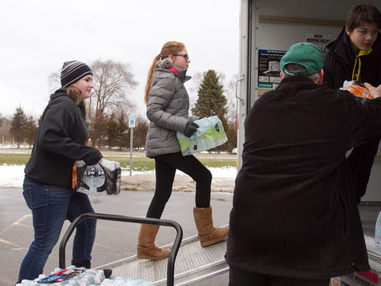 From left, Chloe McGeachy, Chloe Moltzen, Robert Wolff and Salvatore Patierno load water donated from area residents into a rental truck to be delivered to Flint residents. A water drive by Pinckney Area Schools students brought in a big load of bottled water for those in need.