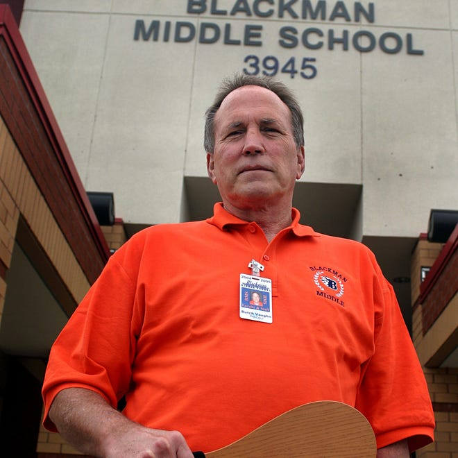 FILE - Butch Vaughn, the former principal at Blackman Middle School holds the paddle that was used at the school.