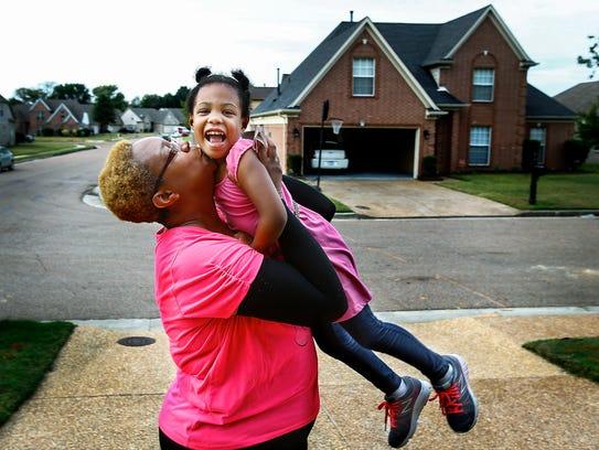 Kari Daniel, a breast cancer survivor, kisses her 3-year-old