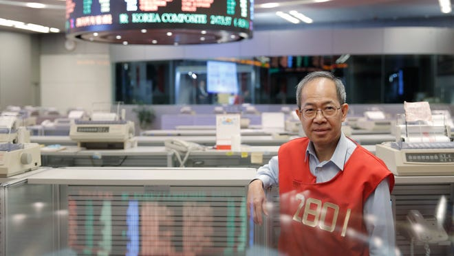 In this Oct. 19, 2017, photo, Yip Wing-keung, a trading manager at local brokerage Christfund Securities, wearing his red trading jacket, poses for a photo at the Hong Kong Stock Exchange. Hong Kong's last remaining stock market floor traders are taking their final orders as the exchange prepares to shut its trading hall, joining other world exchanges in going fully automated.