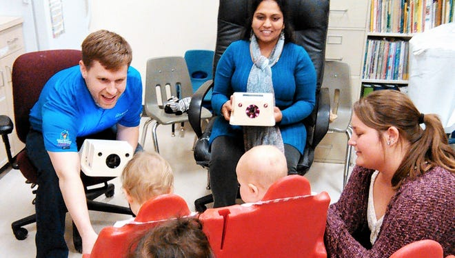 Volunteers Austin Hull, left, and Latha Kempuraj, center, prepare a group of toddlers for eye screening using special hand-held cameras at the Apple Tree Children's Center in downtown Iowa City. At right is Apple Tree teacher Taylor Holterhaus.