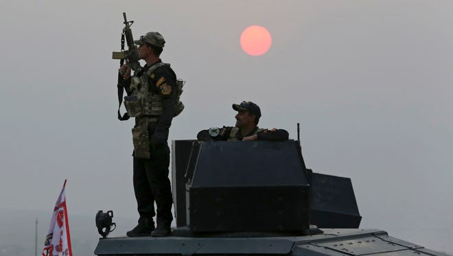 Iraq's elite counterterrorism forces advance toward Islamic State positions as fighting to retake the extremist-held city of Mosul enters its second week, in the village of Tob Zawa, outside Mosul, Monday, Oct. 24, 2016. A convoy of special forces advanced toward the village of Tob Zawa, Monday, encountering roadside bombs and trading heavy fire with the militants.(AP Photo/Khalid Mohammed)