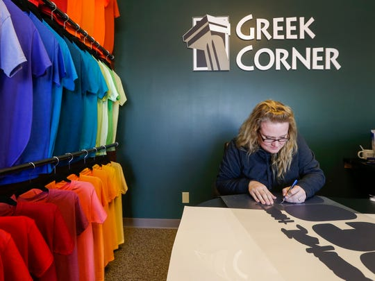 Shelley Abbott cuts numbers out for a jersey at Greek