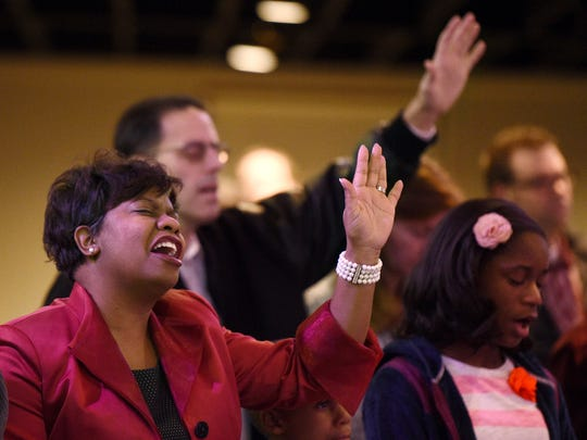Allena Bell, left, and Bob Van Fleteren, in background, lift their hands in praise while singing during church service at Strong Tower Bible Church on Sunday, Feb. 14, 2016 in Nashville.