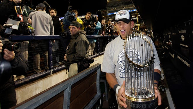 In this Nov. 4, 2009, file photo, New York Yankees' Alex Rodriguez holds the championship trophy after Game 6 of the Major League Baseball's World Series against the Philadelphia Phillies in New York.