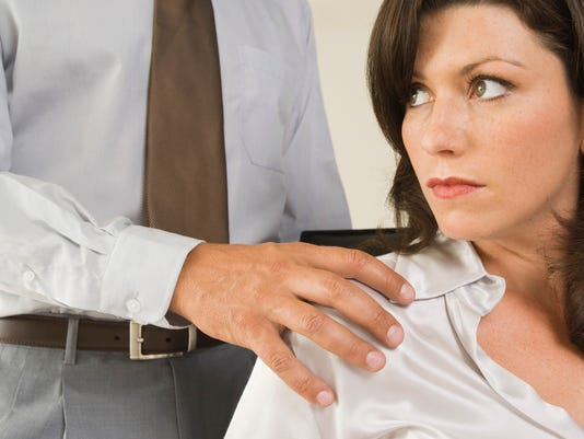 Man touching shoulder of uncomfortable woman co-worker
