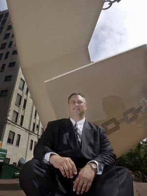 "Chris Cochrane, founder and organizer of the Houdini Days festival, sits in front of the ""Metamorphosis"" landmark at Houdini Plaza in Appleton in this 2004 photograph."