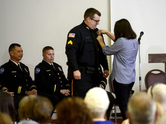 Pensacola Police Department Sgt. Danny Harnett has his badge pinned by his daughter Makenzie on Thursday during a promotion badge pinning ceremony at Bayview Senior Center.