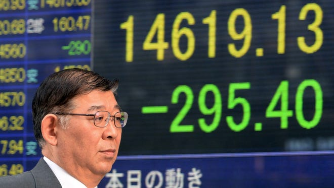 A pedestrian walks past a share price display board in Tokyo on February 3, 2014.