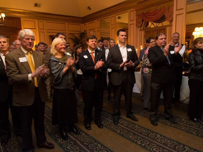 From left, Bill Edwards, Townsend Collins, Catherine Roberson, James Roberson and Eric Elliott applaud during a Commercial Real Estate Awards presentation.