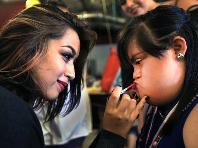 Isabel Garcia (left) helps her cousin, Aeriel Maza, 20, with her makeup before the Miss Magnificent Pageant on Saturday, May 28, 2016.