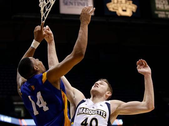 San Jose State's Frank Rogers (14) and Marquette's Luke Fischer (40) get tangled in the net going for a rebound during the first half of an NCAA college basketball game Tuesday in Milwaukee.