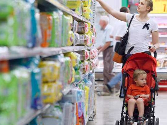 A woman shopping for diapers in the aisle of a store
