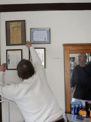 Gary Kiracofe, left, asks for help from his roommate Bobby Yowell while reaching for a framed news article hanging on the wall in his bedroom on Thursday, Jan. 20, 2011. Yowell and Kiracofe once lived in what is now Central Virginia Training Center, a Lynchburg area institution for people with intellectual disabilities. They now live independently in an apartment in Staunton.