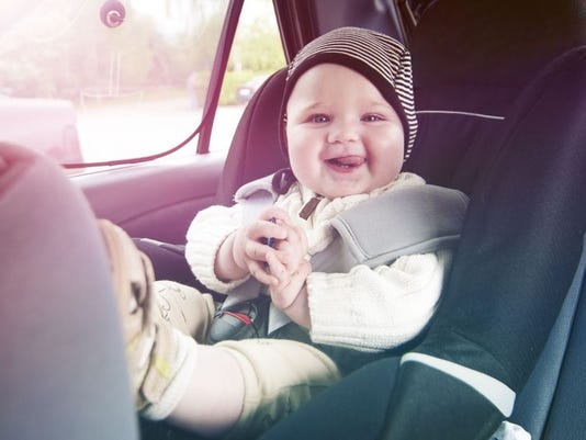 Happy boy is secure in a baby car seat