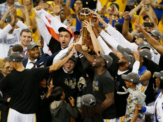 Golden State Warriors players and staff hold up the