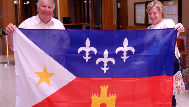 Col. John R. Bourgeois, Director Emeritus of the U.S. Marine Band, and Nada Montgomery, piccolo soloist, check out an Acadian flag gift from Lafayette Mayor-President Joel Robideaux.