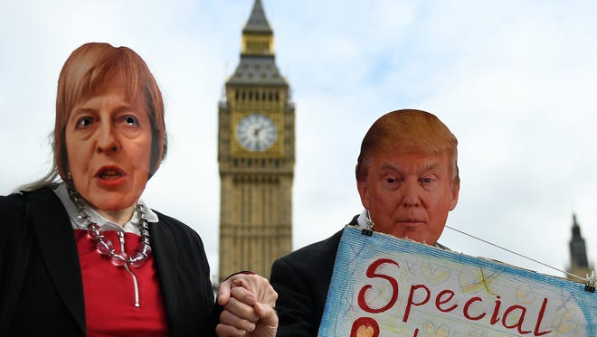 Protesters wearing masks depicting British Prime Minister Theresa May and President Trump and holding hands demonstrate against the proposed state visit to the U.K. of Trump in London, Britain, Feb. 20, 2017.