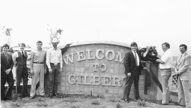From left to right: Ross Smith, Kevin Smith, Eldon Hastings, Bob Lowry, Carl Wilson, Mayor L. J. Reed and City Manager Kent Cooper at the Welcome to Gilbert sign during Reed's tenure as mayor from 1981-87.