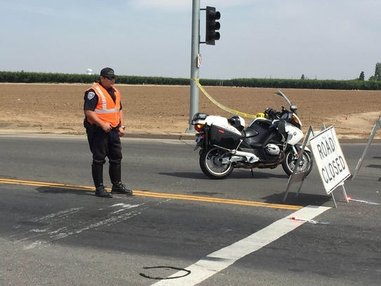 A Dinuba police officer blocks traffic heading West