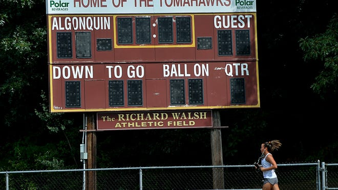 A jogger runs by the scoreboard at the Algonquin Regional High School football field scoreboard Tuesday.  A petition has started to change the name of the school and the Tomahawks mascot, due to objectionable use of Native American imagery and names,  according to the petitioners.