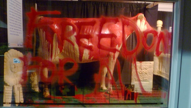 "In this photo provided by Iowans for Animal Liberation is the 2013 butter cow at the Iowa State Fair in Des Moines, Iowa. Authorities confirmed Aug. 12, 2013, that vandals had gained access to the display, poured red paint over the butter sculpture and scrawled, ""Freedom for all,"" on a display window. Police said the damage was cleaned up quickly Sunday morning and the display opened as usual."