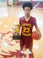 Troymain Crosby poses with Laurel's first boys basketball championship trophy. He scored  10 points as the Golden Tornadoes beat Wayne County 71-47 for the Class 5A title.