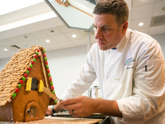 Delaware Technical Community College culinary student James Ankenbrand of Wilmington works on his final exam as he decorates his gingerbread house.