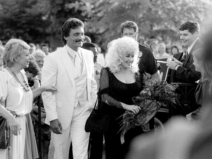 "Dolly Parton, center, is the center of attention as she arrives for the Nashville premiere of her movie ""Rhinestone"" on June 18, 1984."