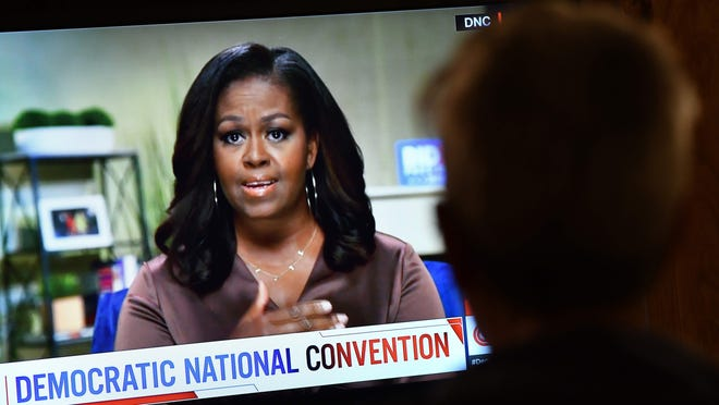 A person watches former First Lady Michelle Obama speak during the opening night of the Democratic National Convention, being held virtually amid the novel coronavirus pandemic, in Los Angeles, on Aug. 17, 2020. On her podcast recently, the former First Lady spoke of feeling down about coronavirus and the struggle for social justice. Psychiatrists thanked her for helping others to voice their feelings.