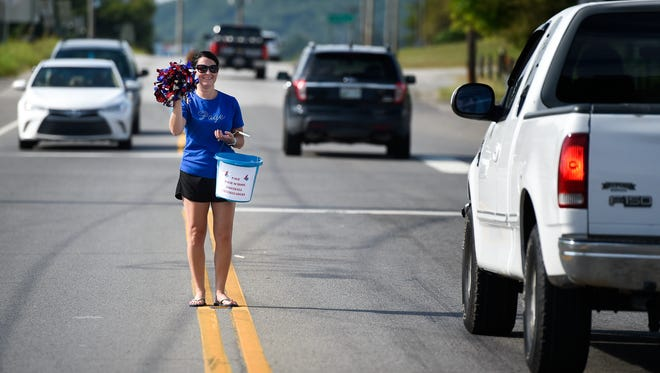 Kim Heath asks drivers for donations  to send the Page High School cheerleading team to finals near the Mexican Market in Triune, Tenn., Saturday, Aug. 26, 2017.