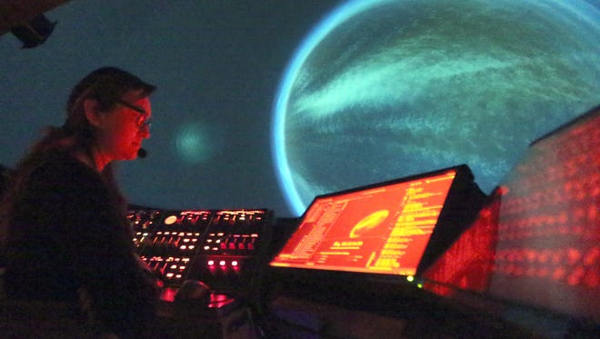Evelyn Maldonado, program manager for the Gene Roddenberry Planetarium at 6531 Boeing Drive, watches the console as planets projected on the domed ceiling fly by during an hourlong presentation to middle school students. The planetarium will move but not close.