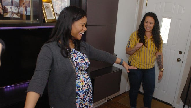 Tiphany Walker notices the stowaway ottomans that offer more seating in her re-designed living room. That's Elizabeth Spencer, IKEA Home Tour team manager watching her reaction.