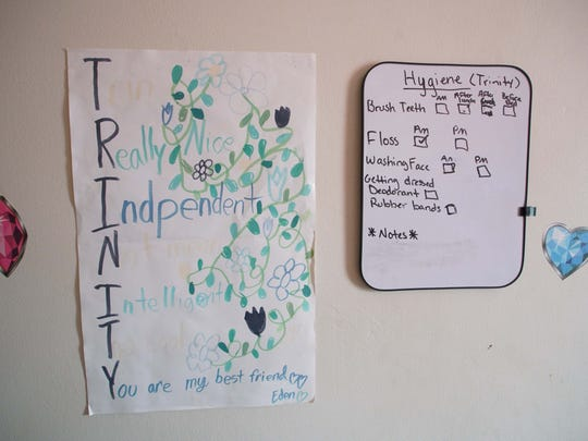 Artwork and a list of daily reminders hang on a wall in Trinity's room.