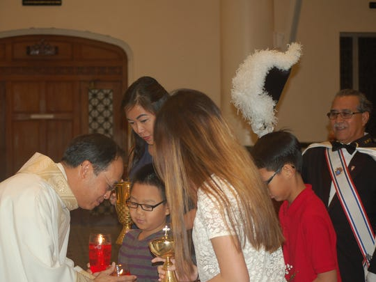 The Rev. Hanh Van Pham (from left) accepts the gifts from his sister, Rose Pham Tran and her children Brayden Tran, Madalyn Tran and Jadon Tran during a Mass of thanksgiving celebrating the 25th anniversary of his ordination to the priesthood Jan. 20, 2017, at Corpus Christi Cathedral.