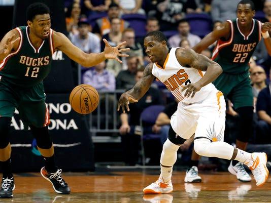 Phoenix Suns' Eric Bledsoe, right, and Milwaukee Bucks' Jabari Parker (12) chase down a loose ball during the first half of an NBA basketball game, Monday, Dec. 15, 2014, in Phoenix. (AP Photo/Matt York)