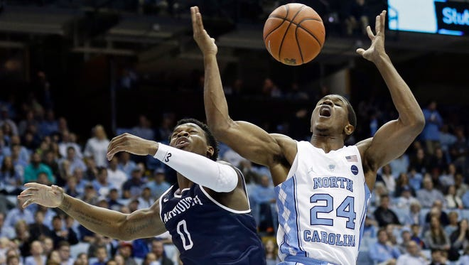 North Carolina's Kenny Williams (24) and Monmouth's Josh James (0) reach for a rebound during the first half of an NCAA college basketball game in Chapel Hill, N.C., Wednesday, Dec. 28, 2016. (AP Photo/Gerry Broome)