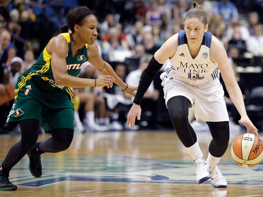 Minnesota Lynx guard Lindsay Whalen (13) protects the ball against the defense of Seattle Storm guard Temeka Johnson (2) in the first half of a WNBA basketball game, Sunday, June 29, 2014, in Minneapolis. (AP Photo/Stacy Bengs)