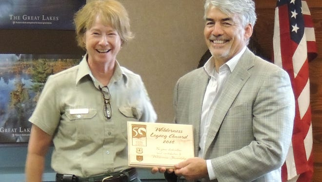 Eastern Region Forester, Kathleen Atkinson, presents Michael Miller, president of Northland College, with a Wilderness Legacy Award at the Northern Great Lakes Visitor Center Aug. 19, 2014.