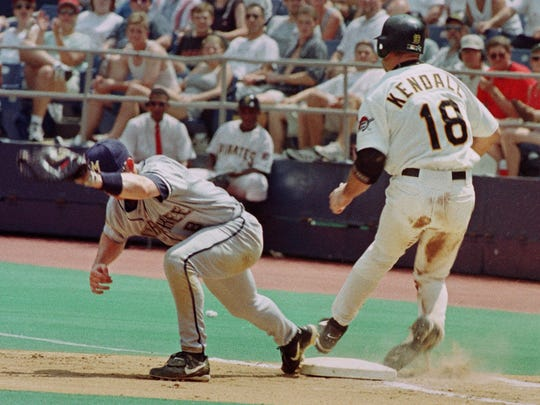 Pittsburgh Pirates Jason Kendall, right, turns his