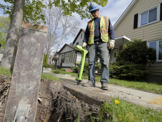 Green Bay Water Utility worker Jamie Phillips looks over a worksite where lead pipes are being removed outside a residence on on Harvey Street in Green Bay.