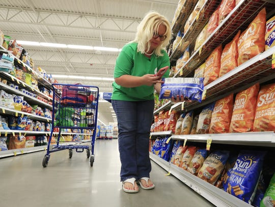 A Shipt shopper fills an online order at a Meijer grocery store in Green Bay, Wis. Shipt is partnering with Hy-Vee to offer same-day grocery delivery in about two dozen markets.