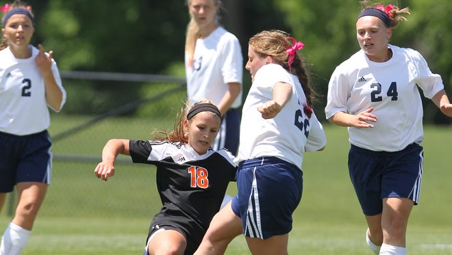 Senior Anna Seydel (18) of the Solon Spartans makes a great slide tackle on the ball against sophomore Lizzy Deprenger (22) the Iowa City Regina Regals during the first round of the IGHSAU Class 1A State Soccer Championships.