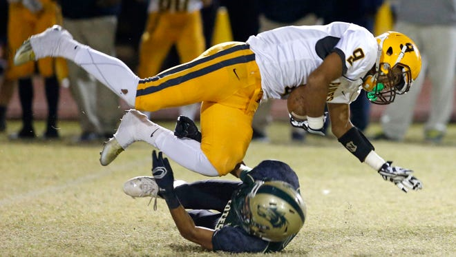 Marcos de Niza wide receiver Marcus Naisant (top) is tackled by Skyline Manny Ruiz during a Division II high school football state semifinal at Mountain View High school in Mesa on November 20, 2015.