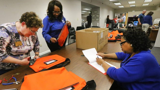 From left, Felicia Hix, Carolyn Peebles, and Frankie Johnson collect the ballots from around Rutherford County at the Rutherford County Election Commission Office on Election Day March 1, 2016. The orange bags are new to this election.
