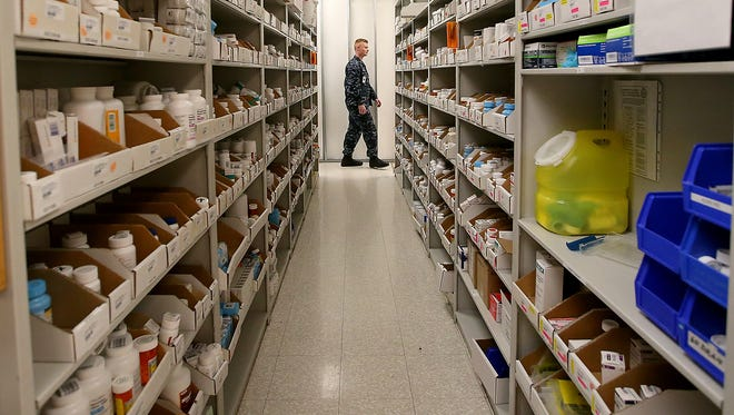 Hospital Corpsman Second Class Ryan Crosson is framed by the shelves filled with medications as he works in the Pharmacy at Naval Hospital Bremerton on Wednesday. The pharmacy is undergoing a renovation that hospital officials say will speed up wait times.
