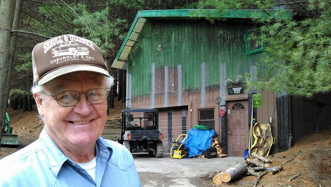 Don Myers smiles in front of the large shed he constructed, which houses the access elevator to his cave.