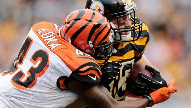 Bengals strong safety George Iloka wraps up Steelers tight end Heath Miller on a reception in the fourth quarter of the Bengals' 16-10 win.